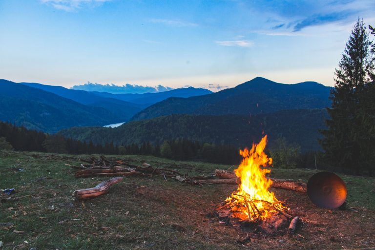 Camping views in the bush over a lake with a camp fire going