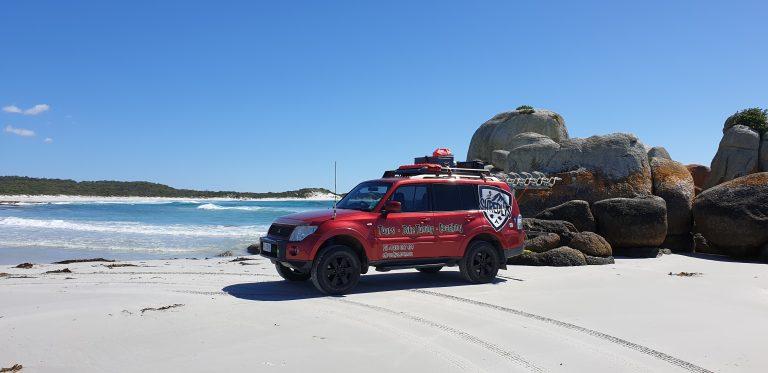 Pajero 4x4 off road tour bus on Bay of Fires beach driving - MTB Tasmania.